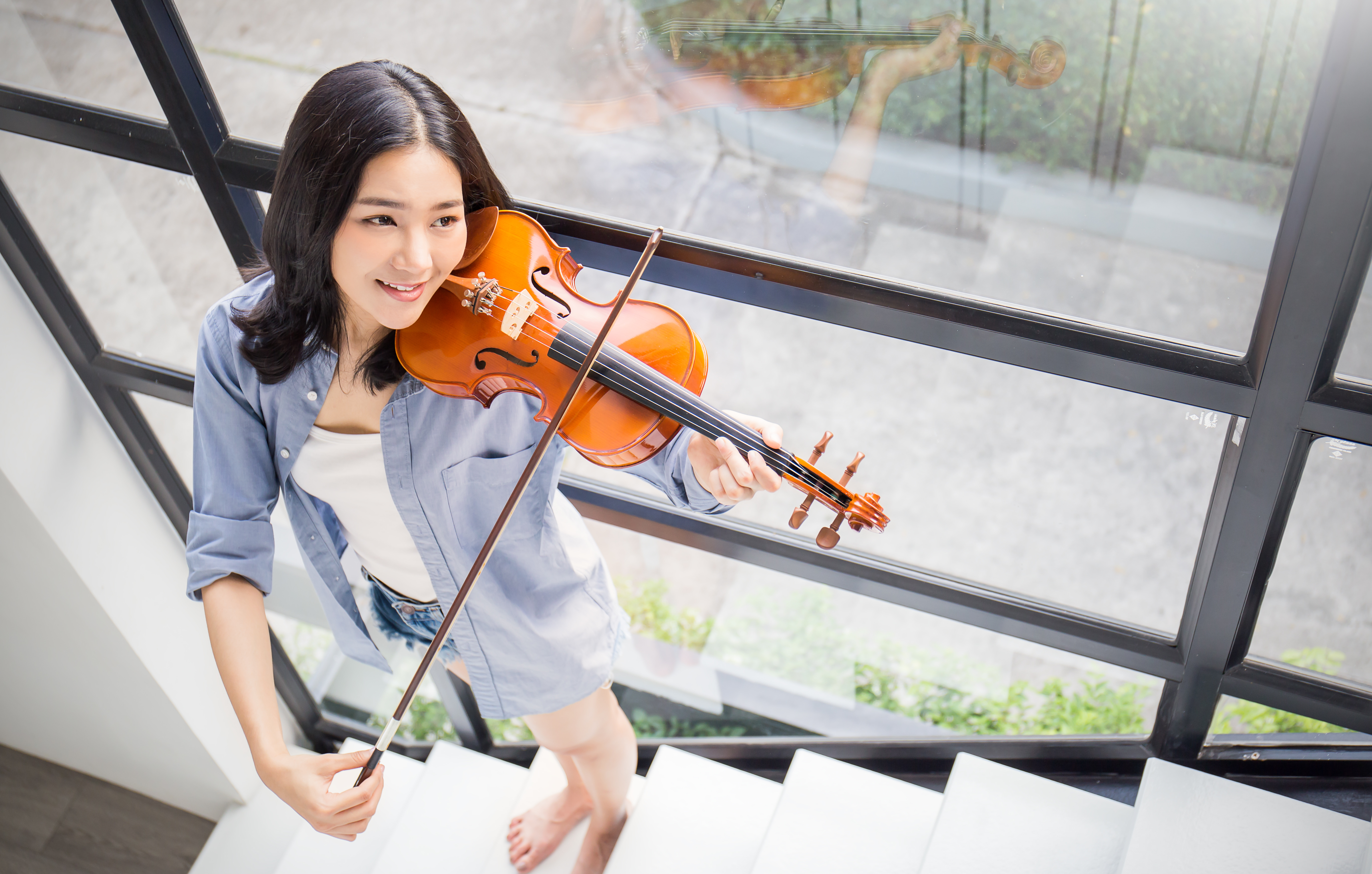 Portrait of beautiful young asian woman playing violin. Education leisure and recreation concept